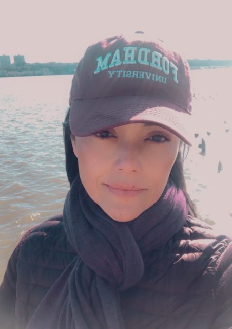 Shenae, wearing a baseball cap from her alma mater Fordham University, standing in front of a body of water